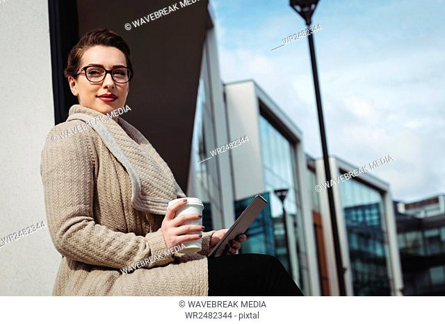 Woman holding disposable cup and digital tablet