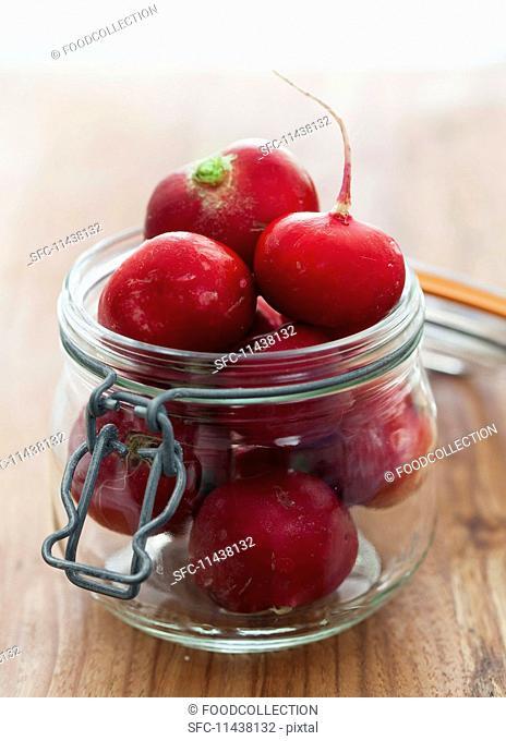 Fresh radishes in a flip-top jar