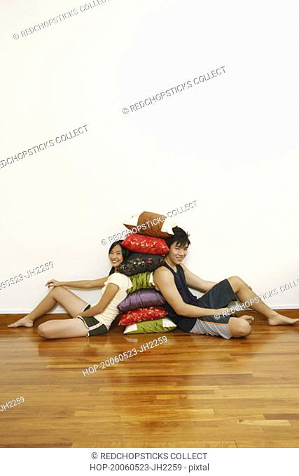 Portrait of a young couple sitting and leaning against a stack of cushions