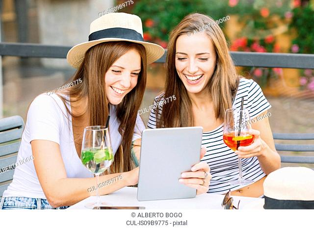 Two young female friends looking and laughing at digital tablet at sidewalk cafe