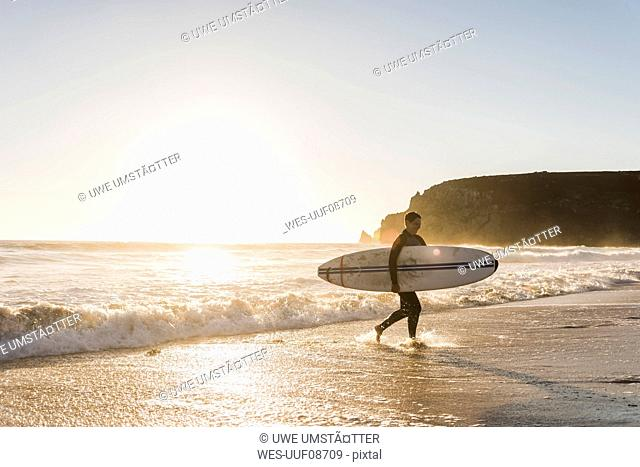 France, Bretagne, Crozon peninsula, woman walking on beach at sunset carrying surfboard