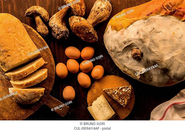 Overhead view of raw and prepared food, cheese, bread, eggs and porcini mushrooms