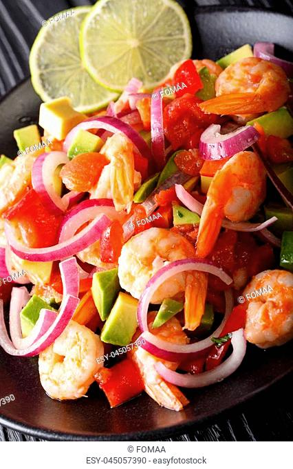 Delicious ceviche of shrimp with vegetables, spices and lime close up on a plate on the table. vertical