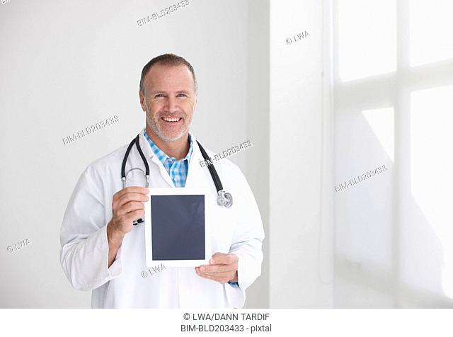 Caucasian doctor holding tablet computer in office