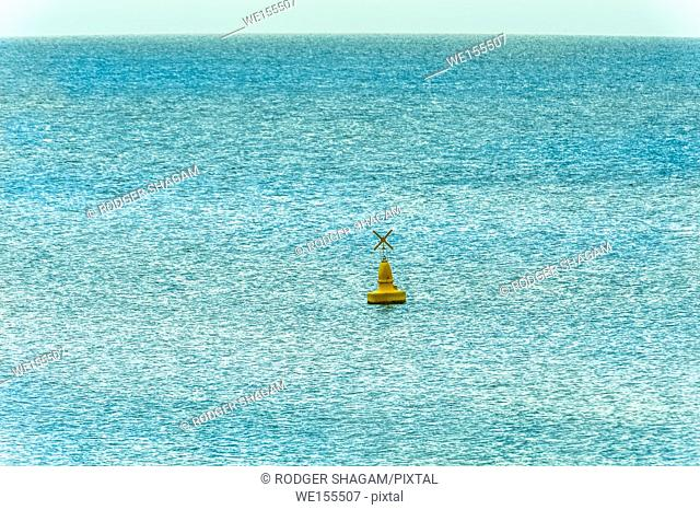 Yellow buoy in the ocean as safety warning and navigation marker at harbor or port. Brisbane, Australia