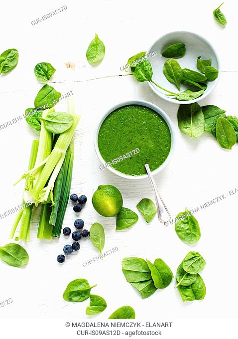 Bowl of fresh spinach soup with celery, spring onions and blueberries