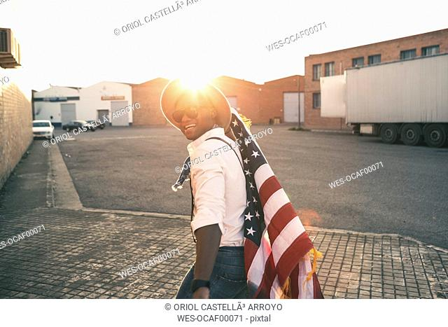Laughing young man with American flag at backlight