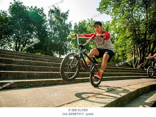 BMX cyclists doing wheelie on steps