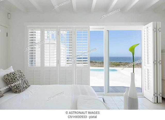 White bedroom home showcase open to swimming pool and ocean view
