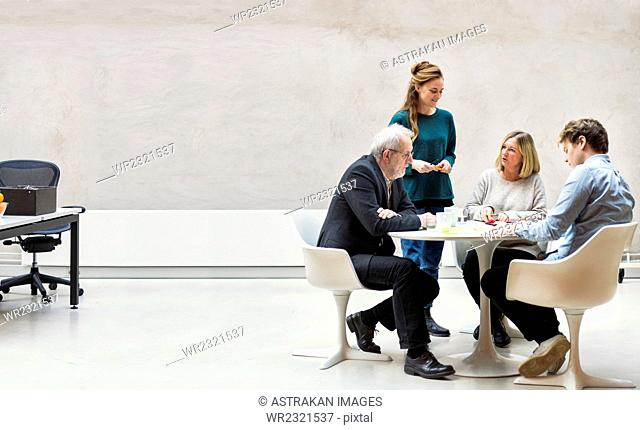 Team of business people having discussion at table in creative office