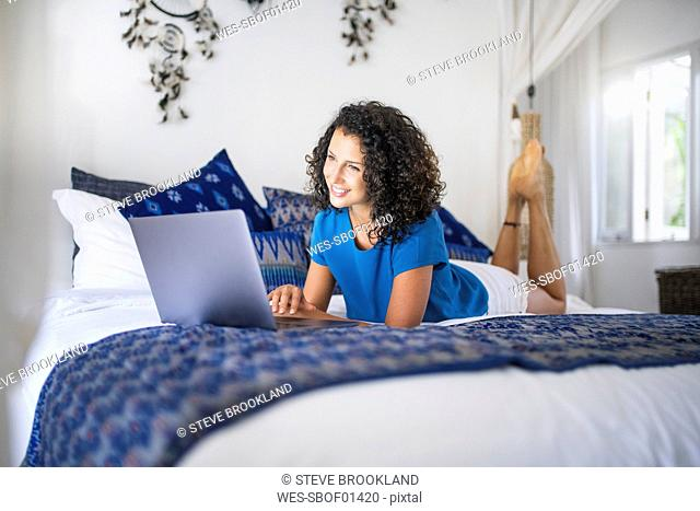 Smiling woman lying in bed using laptop