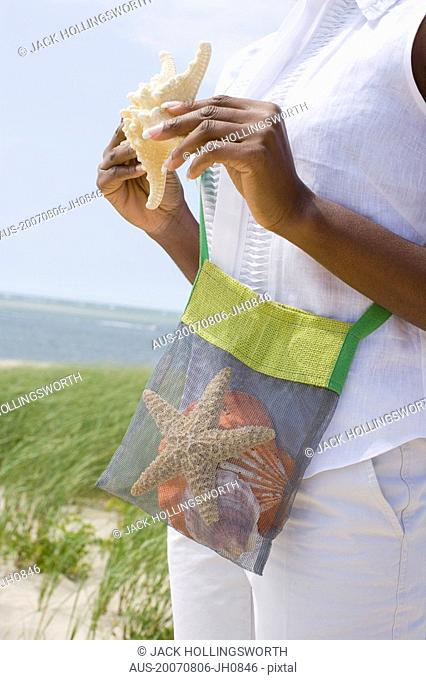 Mid section view of a mid adult woman holding a starfish