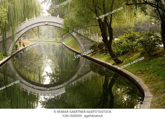 Men fishing in Changhe river with stone bridge in Zizhuyuan Purple Bamboo Park Beijing