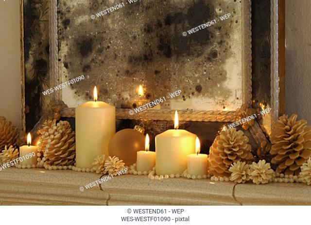 Burning candles with fir cones on shelf, close-up