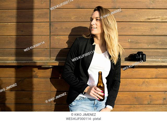 Smiling woman with bottle of beer watching something
