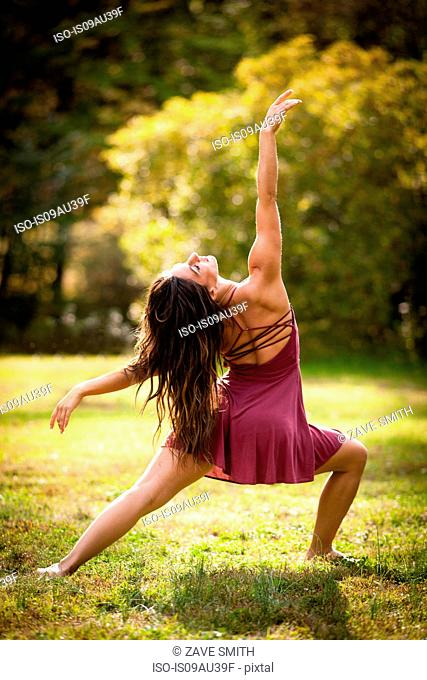 Full length rear view of mid adult woman wearing short dress dancing on grass, head back arm raised