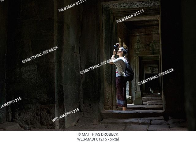 Cambodia, Siem Reap, Angkor Thom, tourist taking pictures of Bayon temple with camera