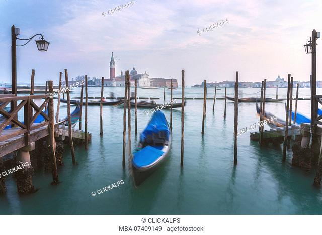 Gondolas tied up to wooden poles on the Canal Grande, in the background the monastery of San Giorgio Maggiore, Venice, Veneto, Italy