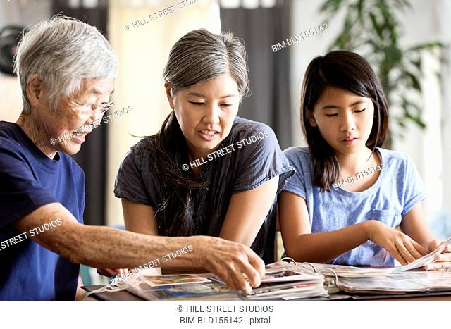 Three generations of Asian women looking at photo album