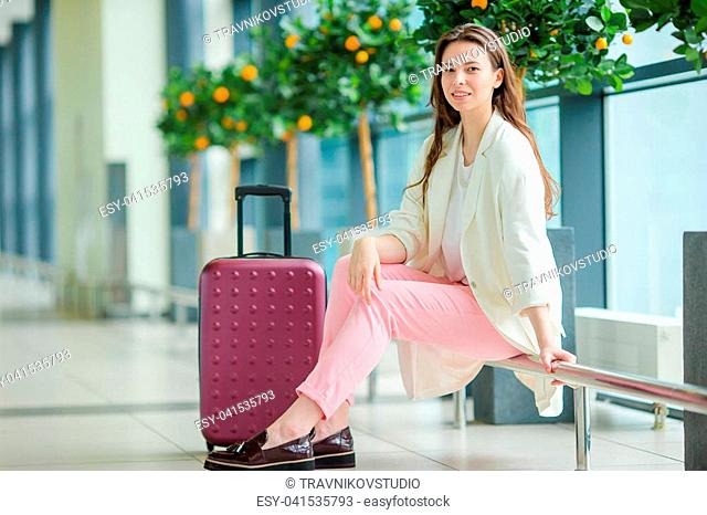 Young woman in international airport walking with her luggage