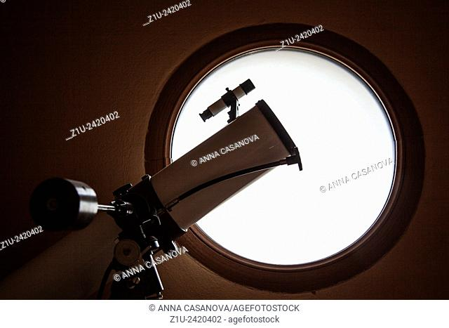 Telescope silhouette in front of round window