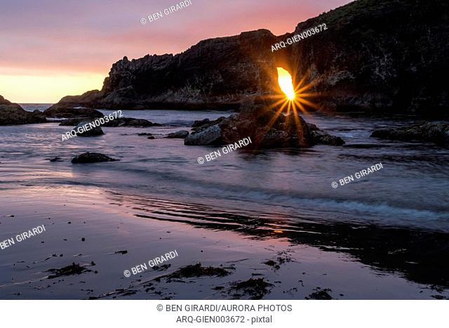 Majestic natural scenery with Sun shining through hole in rocky outcrop at Second Beach at sunset, La Bush, Washington State, USA