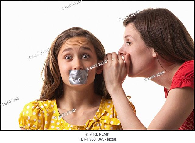 Woman whispering to a frightened girl