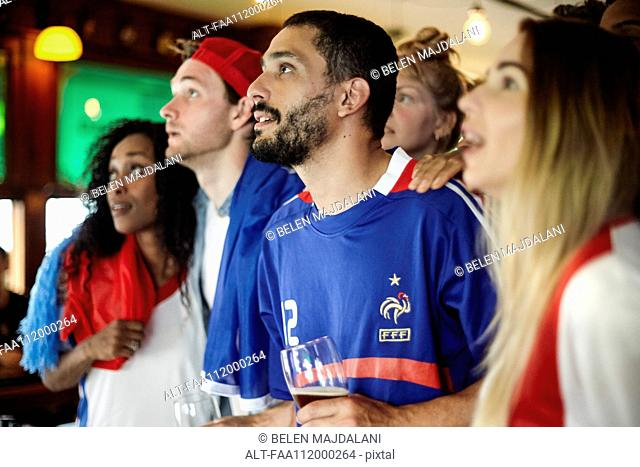 French football supporters watching match in bar