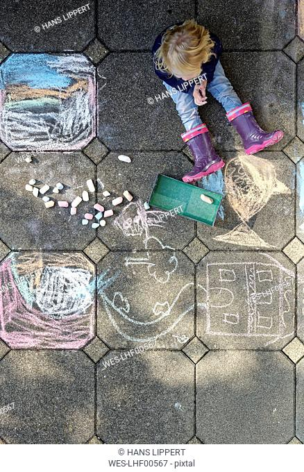Little girl after drawing with chalk outdoors, top view