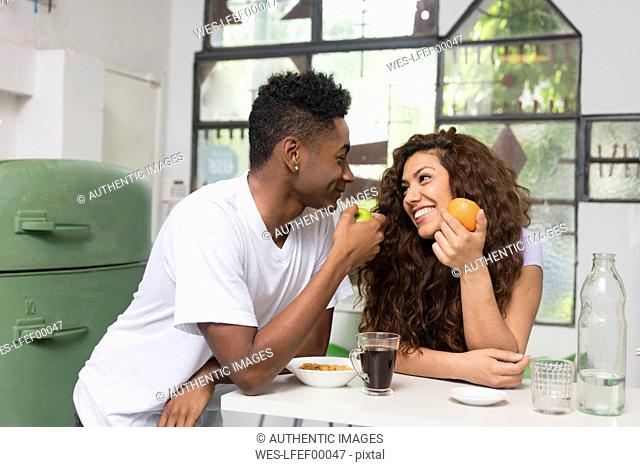 Smiling young couple eating fruit in the kitchen