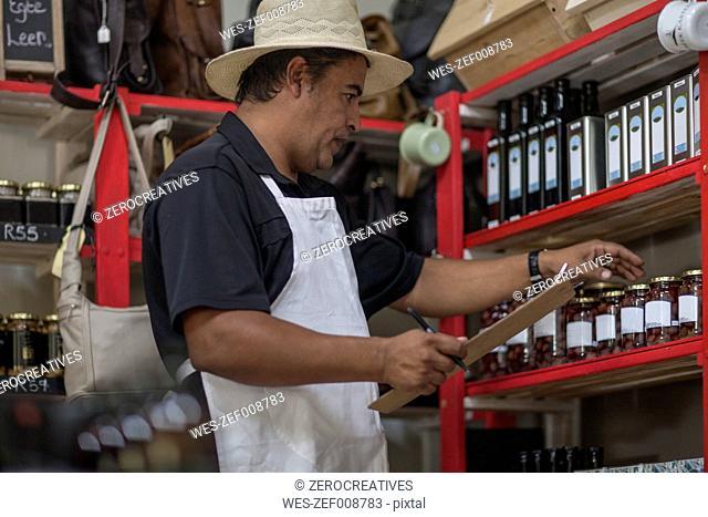 Shopkeeper in shop taking stock