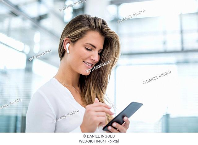 Smiling young woman wearing in-ear phone using cell phone