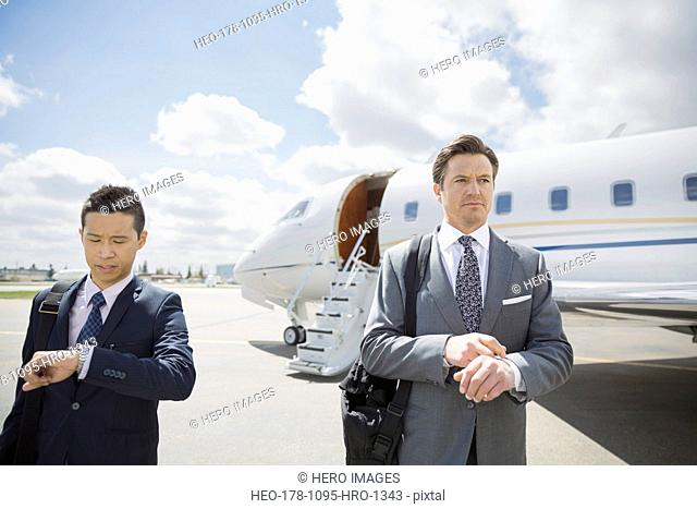 Businessmen checking wristwatches on tarmac with corporate jet