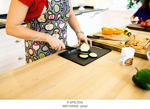 Midsection of mother chopping egg plant in kitchen
