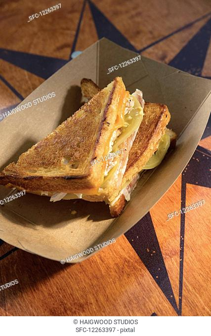 Grilled cheese cut in triangles and served in cardboard bowl