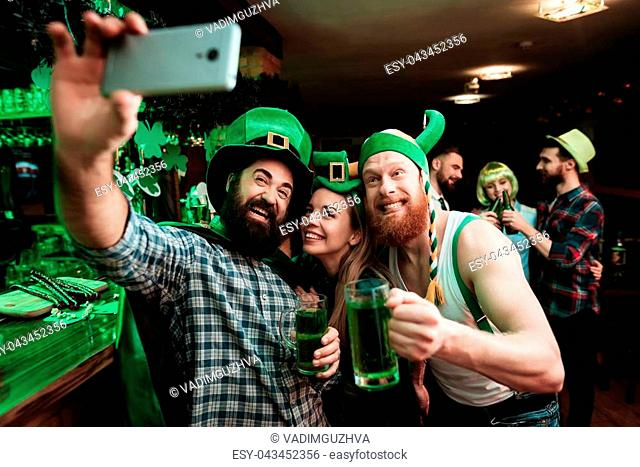 Two men and a girl in carnival caps do selfie at the bar. They celebrate St. Patrick's Day. They are having fun