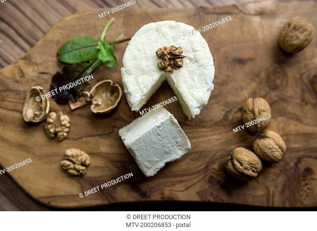 High angle view of cheese and walnuts on a chopping board, Germany