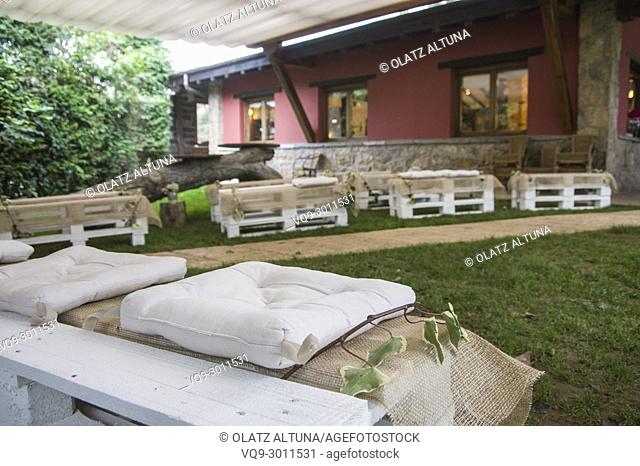 Garden center decorated for wedding party with wood benches in Jai Alai restaurant, Urrestilla, Basque Country, Spain