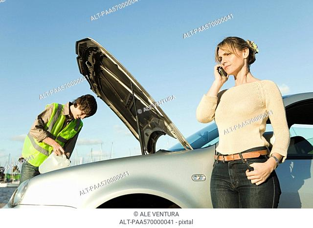 Woman making phone call while roadside assistance mechanic works to repair car
