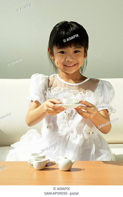 Girl with tea set in hands smiling at camera