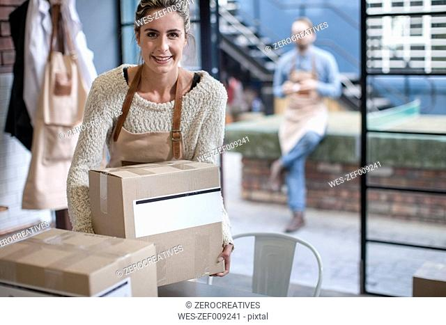 Smiling young woman with cardboard box
