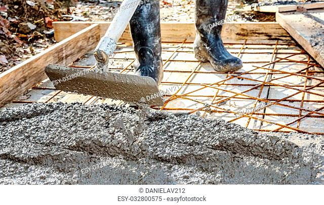 Worker with gum boots spreading ready mix concrete