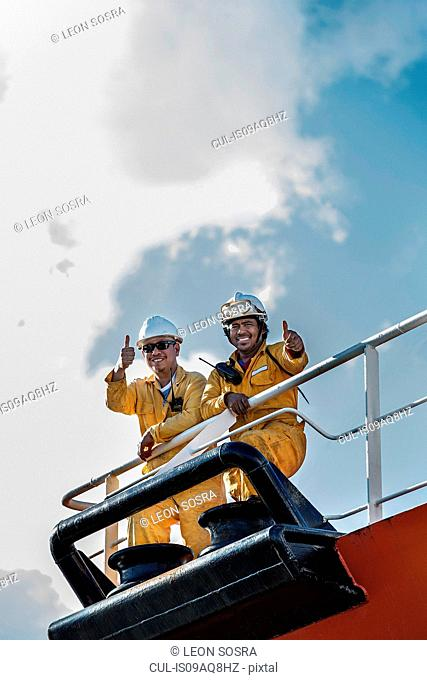 Portrait of two workers on oil tanker giving thumbs up