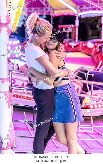 Mother and daughter hugging at fair