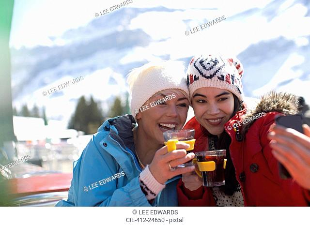 Friends in warm clothing taking selfie outdoors