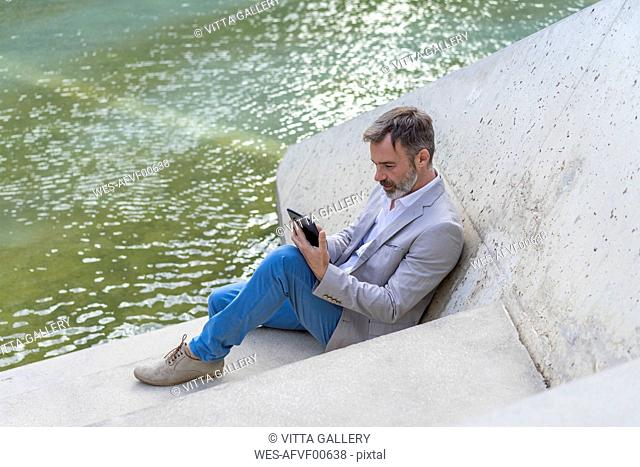 Businessman sitting on steps outdoors using tablet