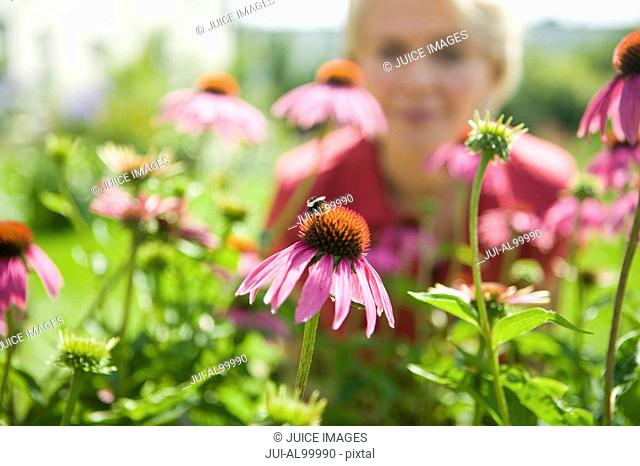 Woman looking at bee on flower