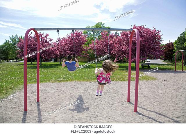 Mother and 4-yr-old daughter on swings in spring, Markham, Ontario, Canada
