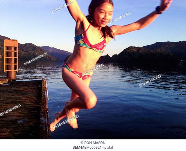 Mixed race girl jumping from dock into lake