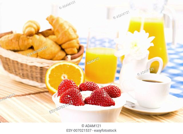early breakfast, juice, croissants and strawberries with cream, still life